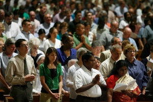 A large crowd of Catholics at prayer during Mass.